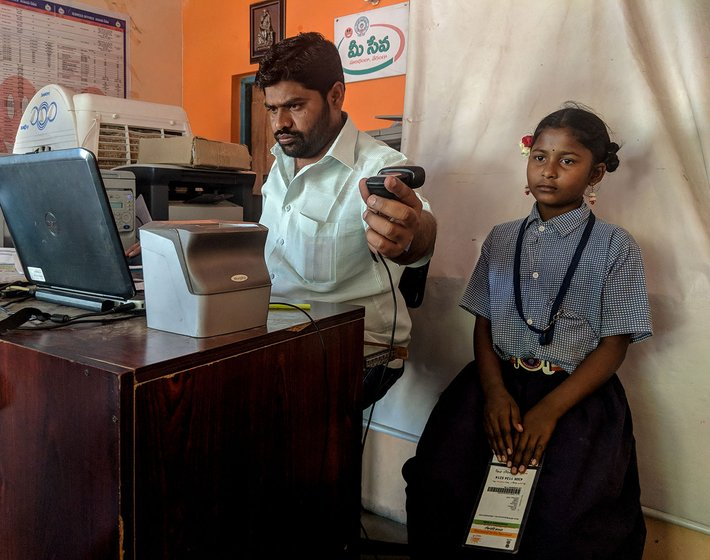 A man sitting at a desk in an office taking a photograph of a young girl in a school uniform. She is holding her Aadhaar card.