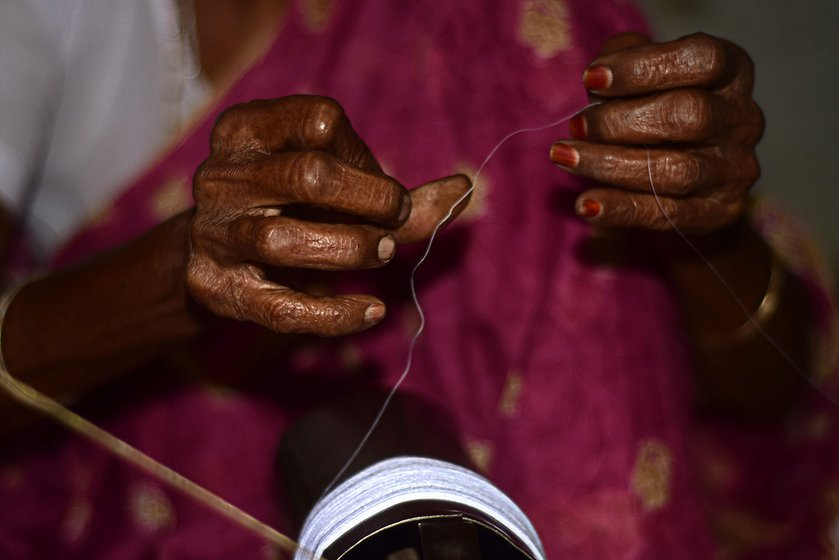 Shakuntala, 90 years old, spins the cotton thread using the charkha; she has been doing from the age of 20