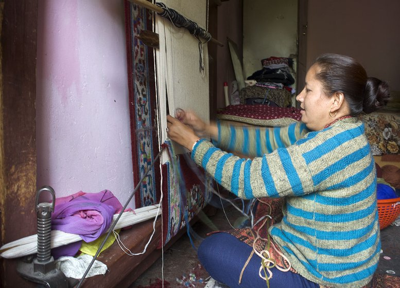 Woman weaving a carpet inside her home.