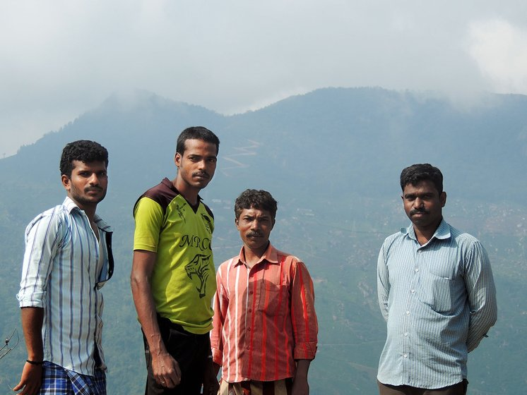 Four young men standing together with the mountains in the background