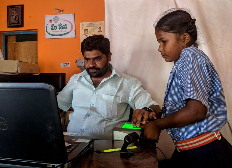 A man sitting at a desk in an office taking the biometrics of a young girl in a school uniform.