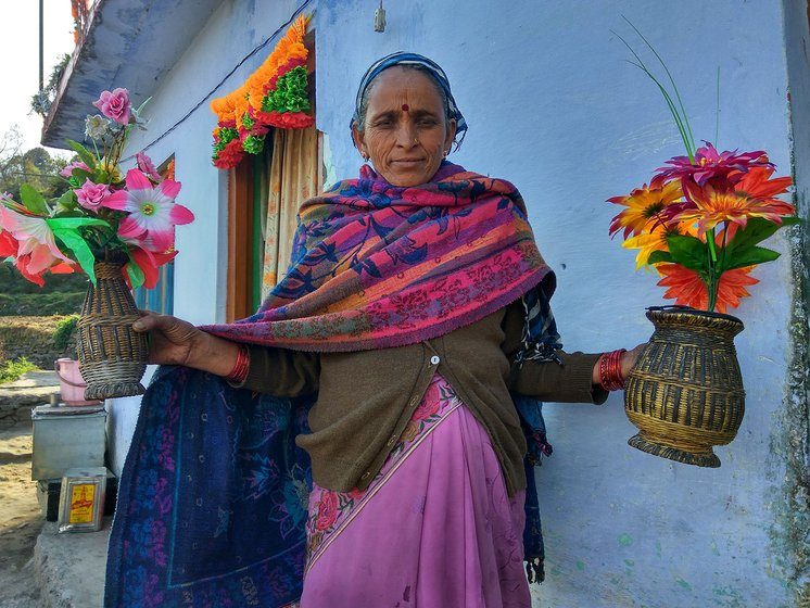 A woman standing outside her house holding two woven bamboo vases filled with plastic flowers