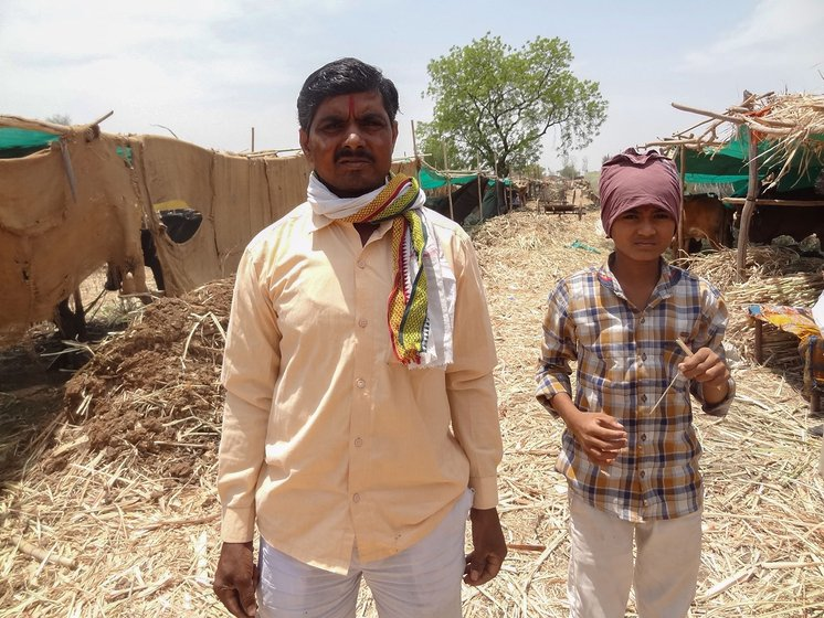 Prahlad with his youngest son Vijay, a seventh grader, at the cattle camp
