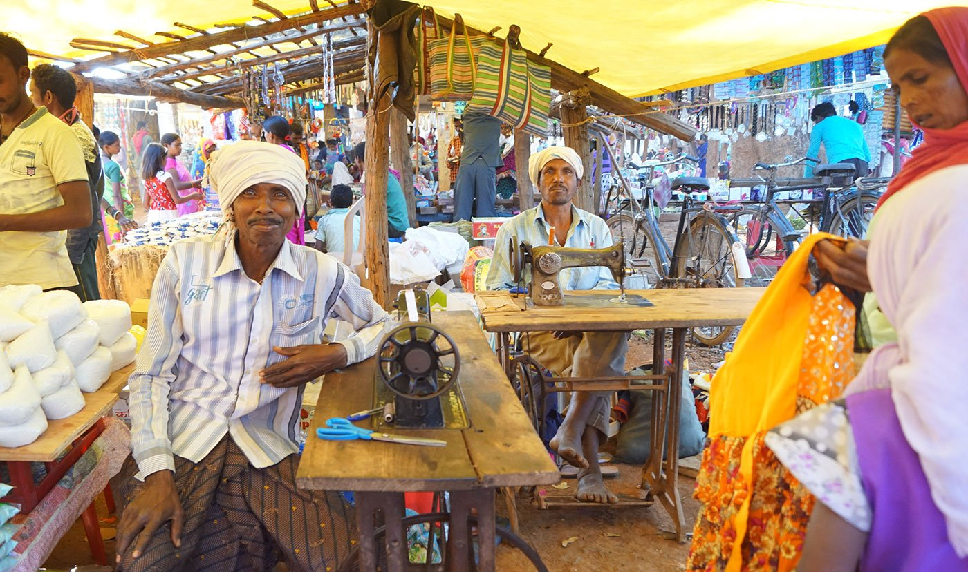 Massuram Padda (at the back) from Bagjor village and Ramsai Kureti from Ture village have brought their sewing machines here on bicycles. They will alter and repair torn clothes at the haat, and make around Rs.200-300 each