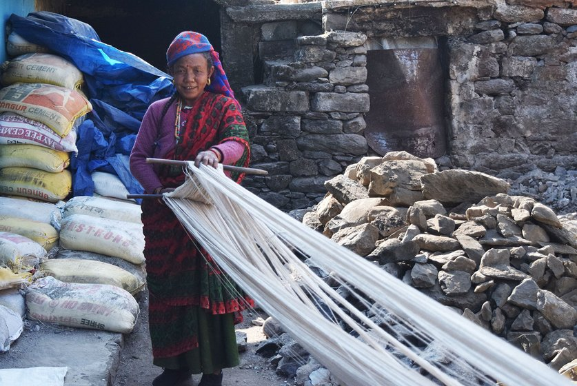 Woman holding up weaving thread outside her home.