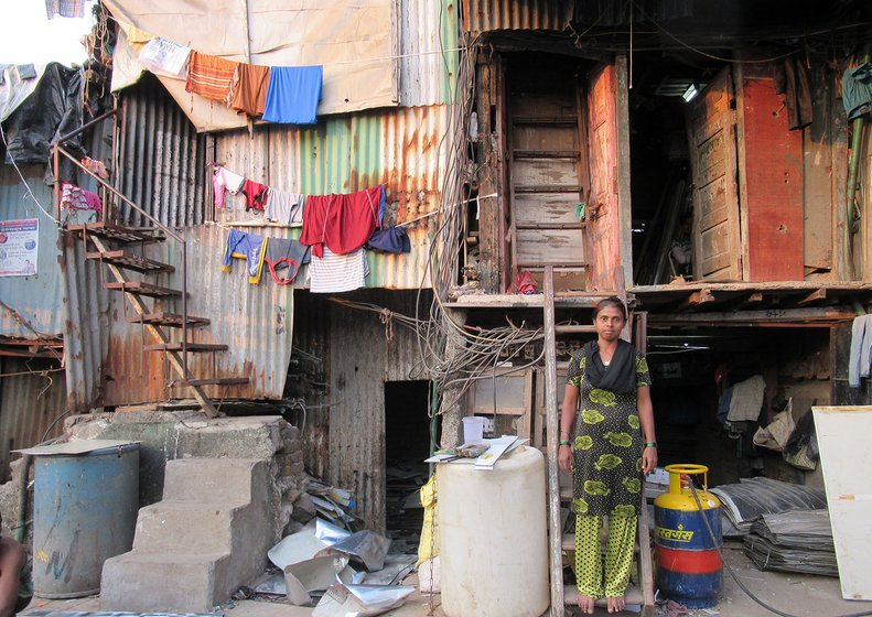 A woman standing on a ladder amidst hutments in Dharavi, a slum in Mumbai