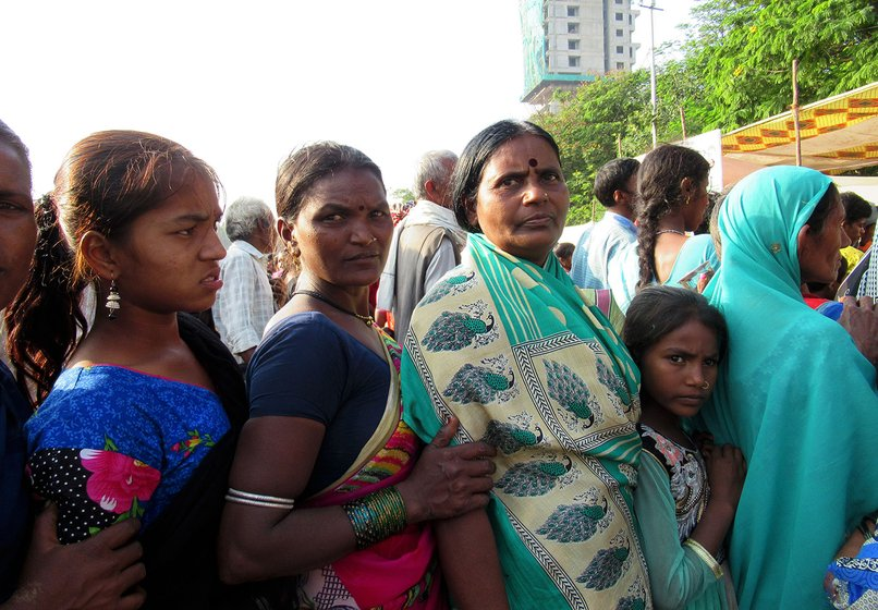 Baby Suretal (woman in green saree) waiting in line for biscuits along with some other women