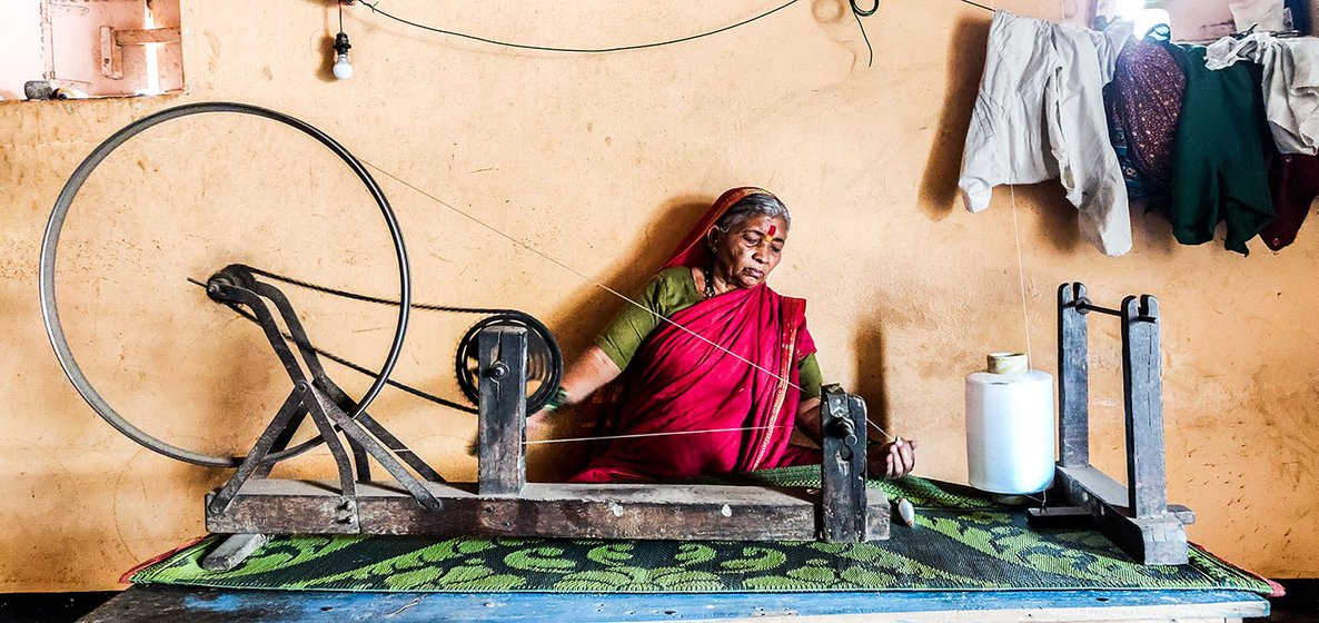Vimal Tambe hand spinning the polyester thread which is wound on a pirn