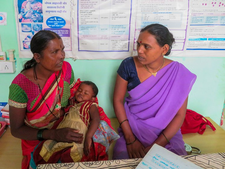 Chandrakala checking a baby at primary health centre