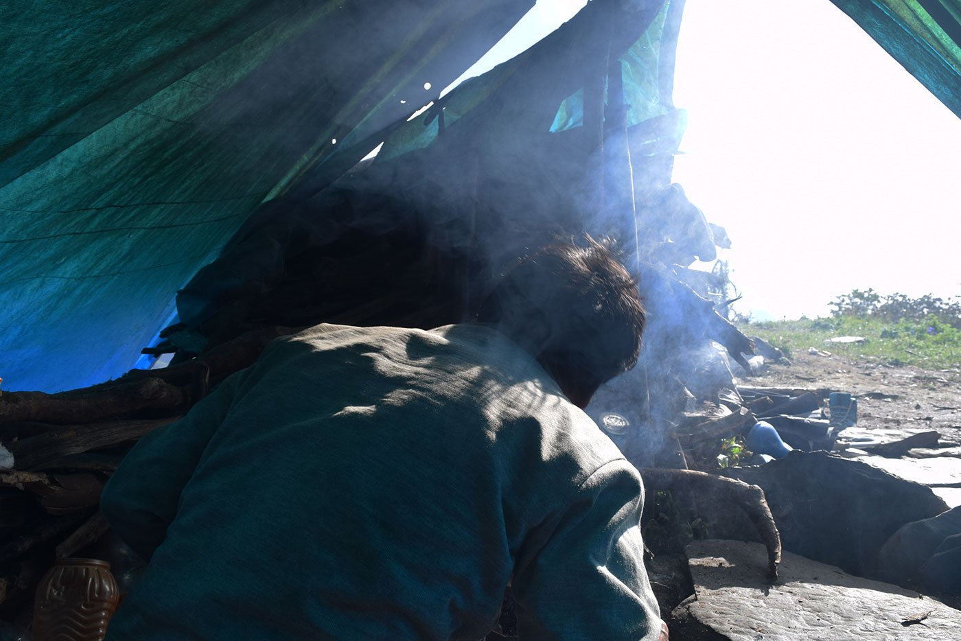 Smoke bellows from the camp while Gopal Singh makes food in the morning before he leave for the hunt