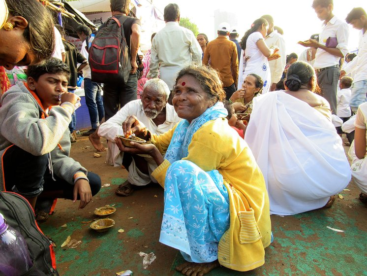 Shantabai Kamble sitting with her husband (old man in the background) and other people eating food