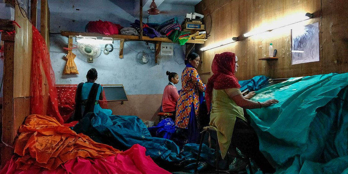 Women at work in a textile factory in Mina Nagar as they cut extra threads off the saris. They clock in 8 hours of work every day between 9am to 5pm, and earn an average of Rs. 5,000-7,000 per month