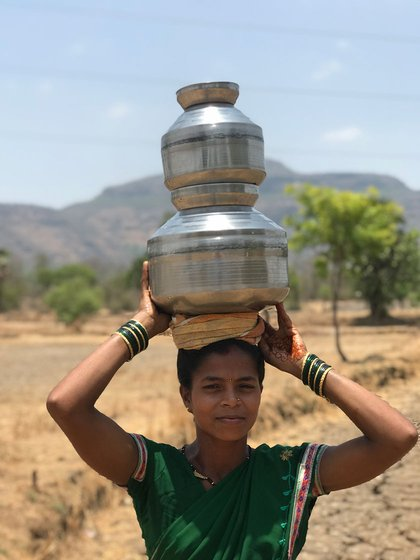 Deepali Khalpade (who shifted to Man pada) carrying pots of water on her head