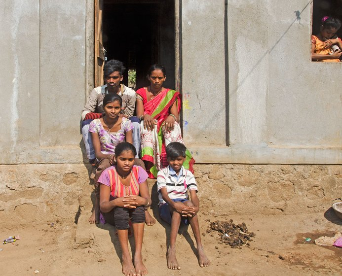 Tulshi with her children Kashinath (top row left), Munni (2nd row), Geeta (3rd row left) and Kashinath (3rd row right), sitting in the doorway of their house