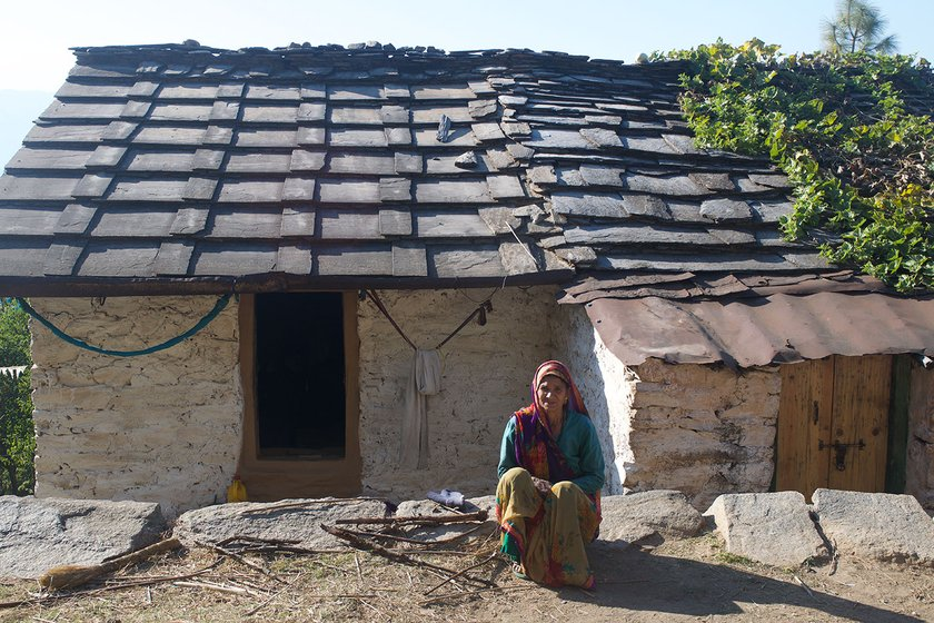 A woman sitting outside her home in a village in Uttarakhand