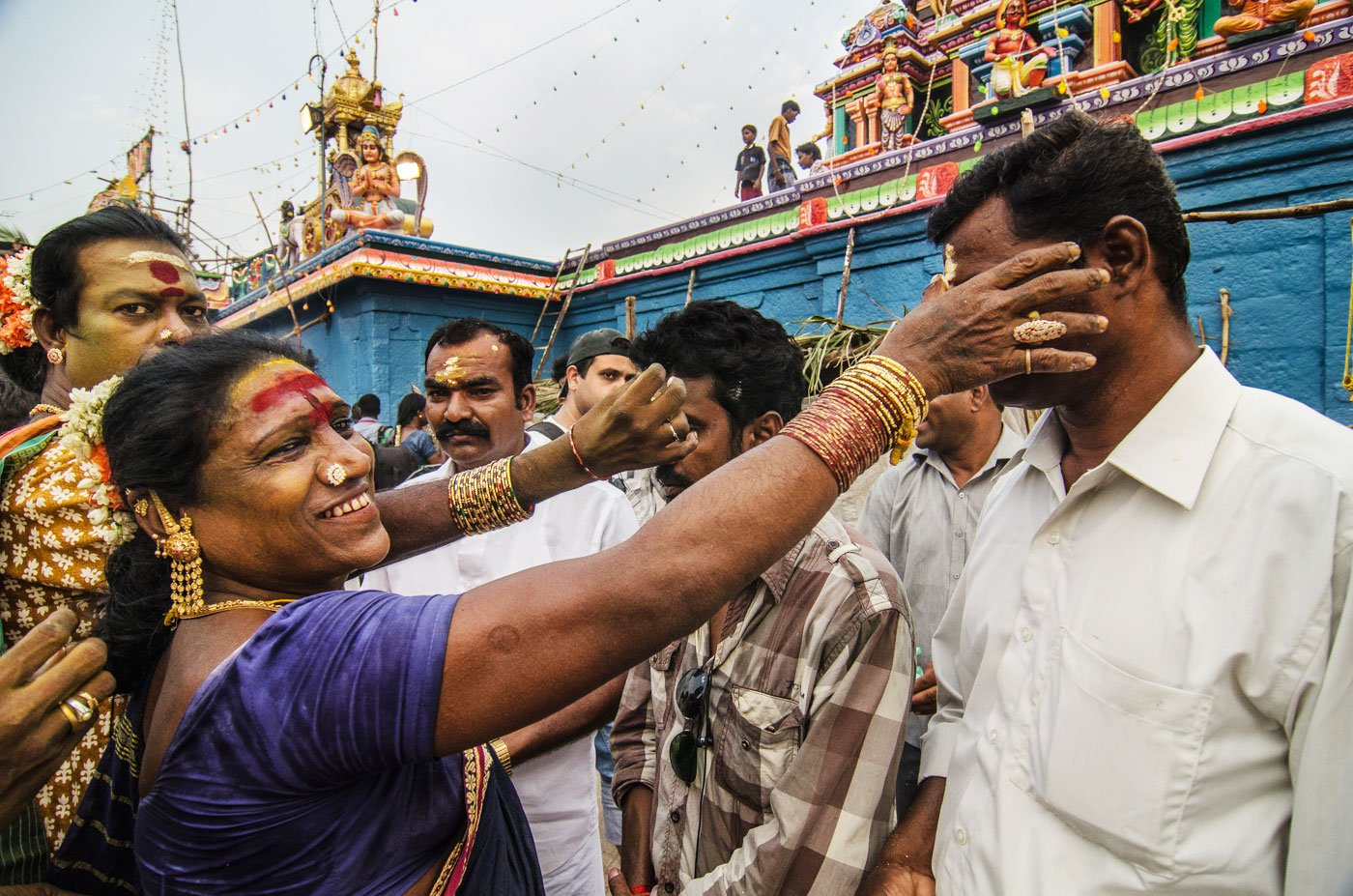 Despite the social ostracism that transgender women face, people also regard them as 'lucky'. They gather outside the Koothandavar temple to receive blessings from aravanis.