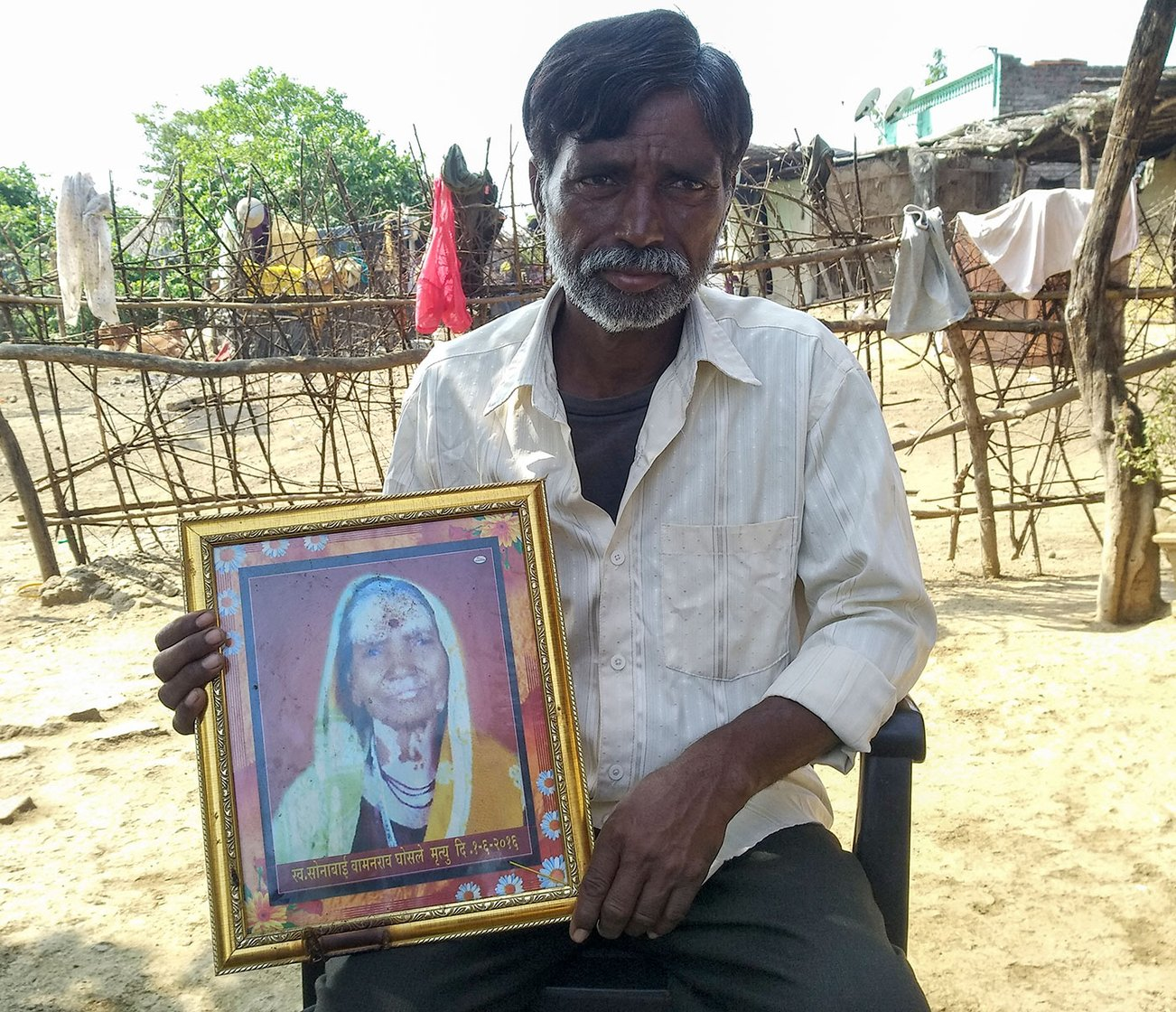 Subhash Ghosale, a tribal farmer in village Borati, holds the photo of her mother Sonabai Ghosale, T1's first victim. She died in T1's attack on her field close to the village on June 1, 2016.