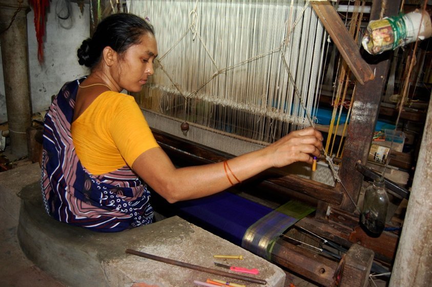 Lakshmi weaves a silk-cotton saree. She herself wears a synthetic one