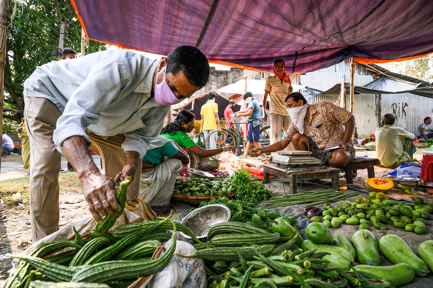 "Customers picking up vegetable from Parimal Dalal's stall. After 30 years of doing this work, 51-year-old Parimal, is more confident than the others, and says, ""My business hasn't changed much. Customers I am acquainted with are coming here too."""
