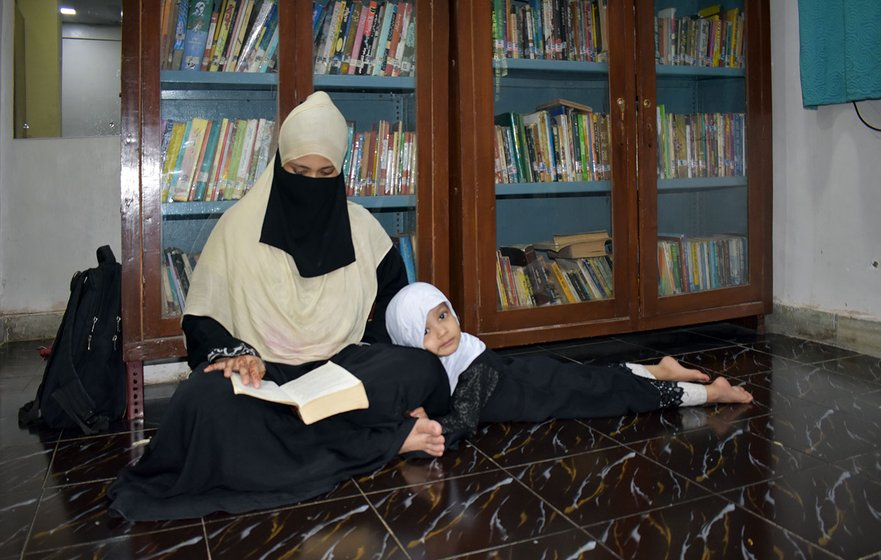 Shafiya Shaikh reads as daughter Misbaah Fatima, 4, looks on