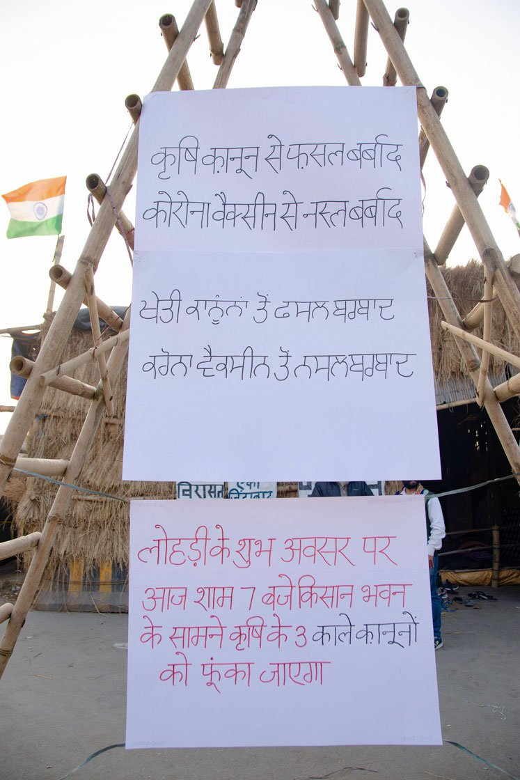 Left: Posters announcing that the three farm laws will be burnt at 7 that evening on the occasion of Lohri. Right: Farmers raise slogans as the Lohri fire burns.