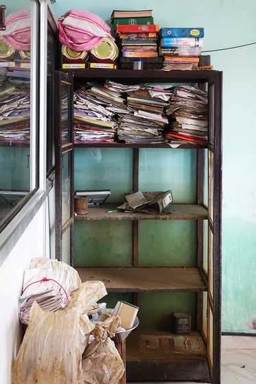 Documents and books stacked on a shelf