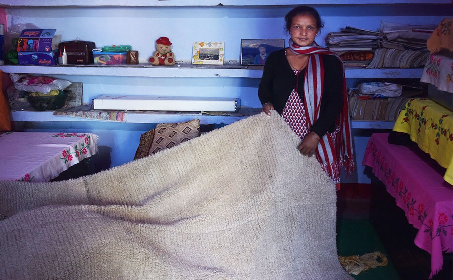 Woman showing a thick banket (chutka) inside her home.