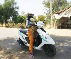Woman standing with scooter