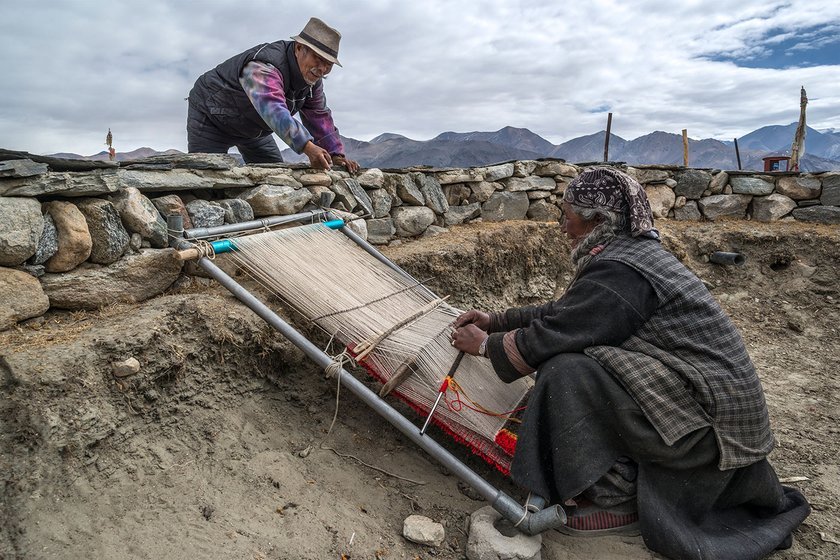 Tsering Dondap and his wife Yama chat as she weaves a carpet on the bank of Pangong lake in Spangmik village, around 60 kilometres southeast of Tangste town