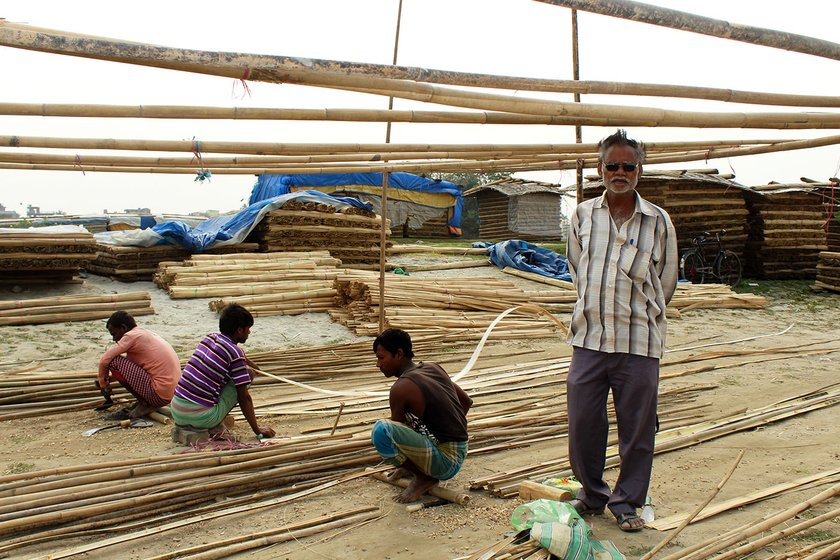 Radhakrishna Mandal (extreme right), is a contractor. Workers working on bamboo in the background.