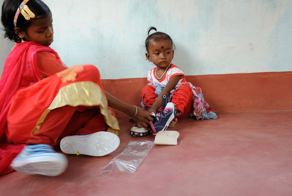 A little girl who has not yet been named gets her first pair of shoes from a non-governmental organisation