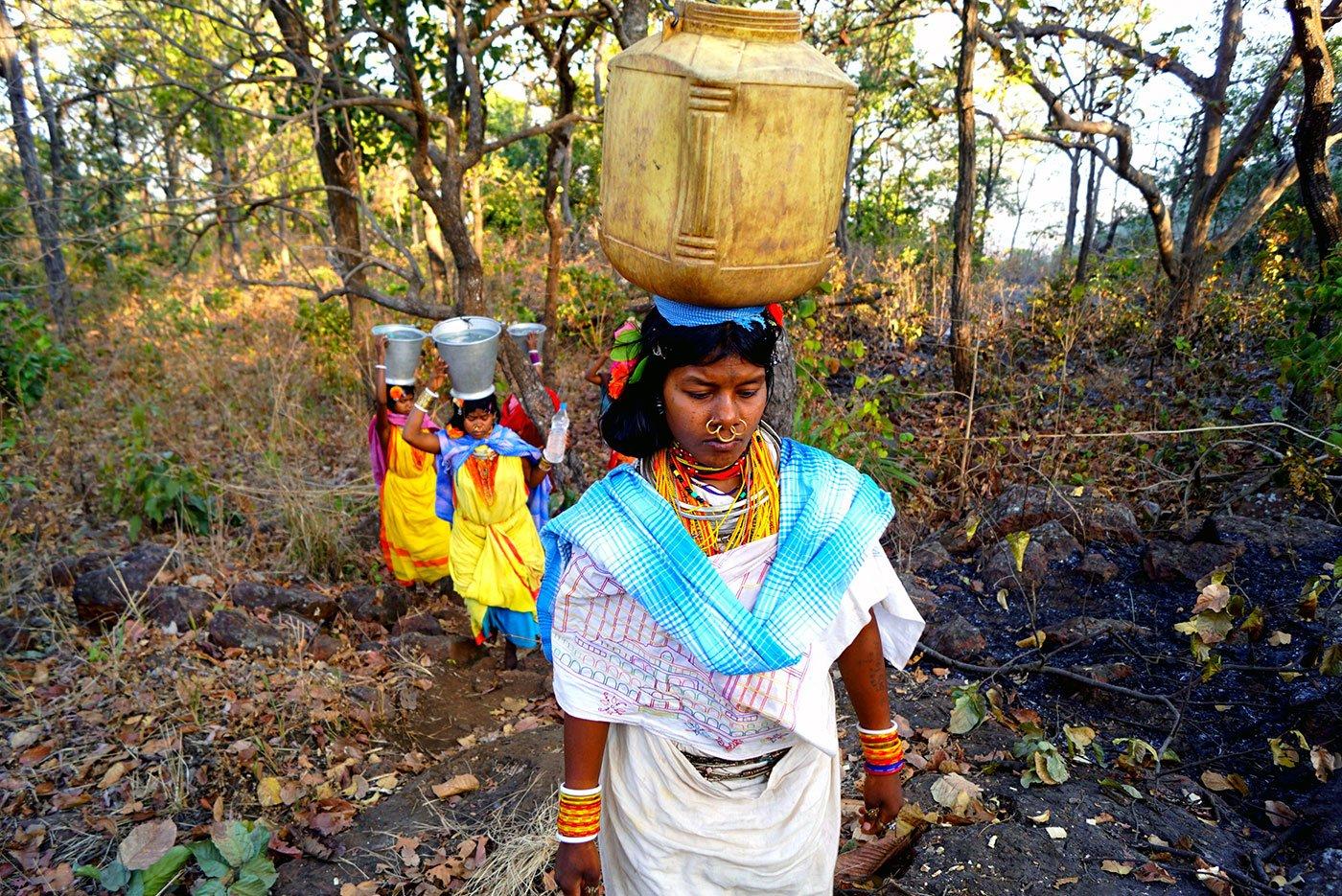 Tribal women walking uphill carrying water on their heads