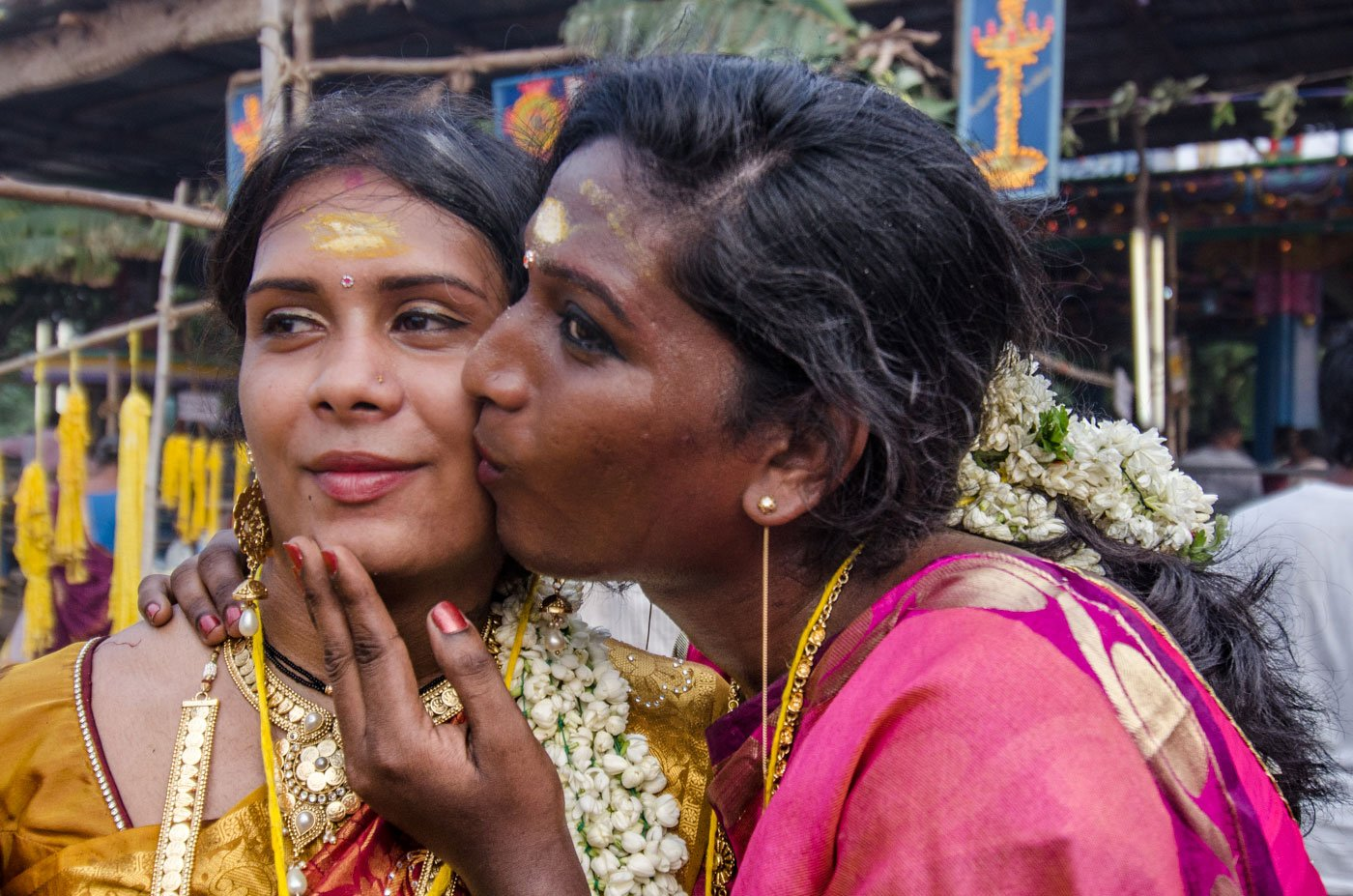 Once they've tied the knot, the aravanis rejoice. Pinky (right), in a gleeful moment, kisses her best friend and sister bride Mala. A transgender woman kisses another transgender woman on the cheek.