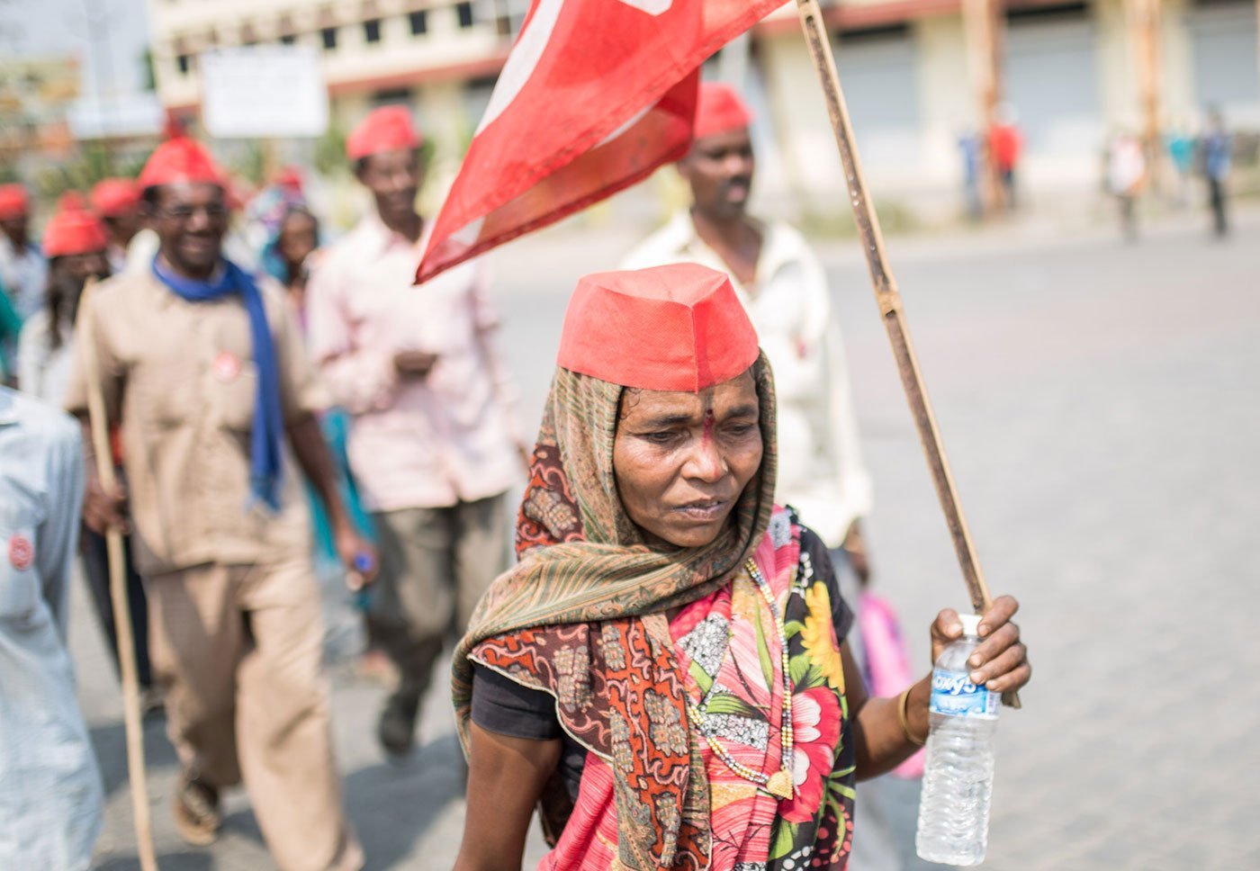 A woman marching alongside others, holding a red flag and a plastic bottle in her hand