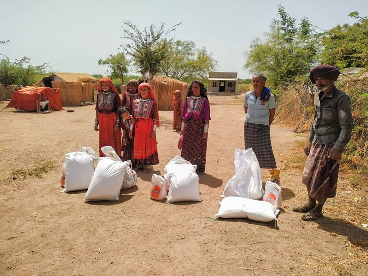 Left: Pastoralist families receiving ration bags from Bhikhabhai Vaghabhai Rabari, president of the Kachchh Unt Uchherak Maldhari Sangathan (Kachchh Maldhari Camel Herders Organisation). Right: Several Fakirani Jat families have received such ration kits from a Bhuj-based organisation working for the rights of the maldharis. The bags include essentials like wheat, lentils, cotton oil, turmeric, spices, salt and rice. The families say this has reduced the pressure on them greatly.