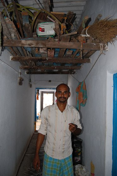 Right: Napa Kumar stands beneath the attic in which his loom lies packed away