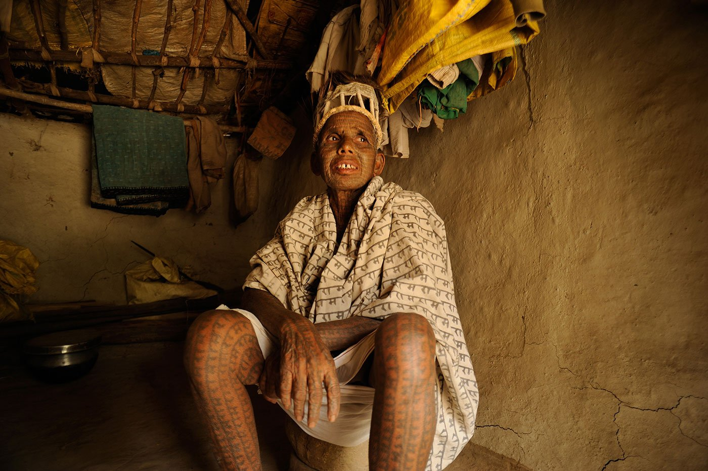 Old tattooed woman sitting in her mud house