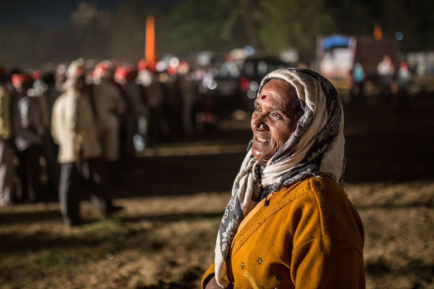 A woman with her head covered standing at Somaiya ground, Mumbai, at night
