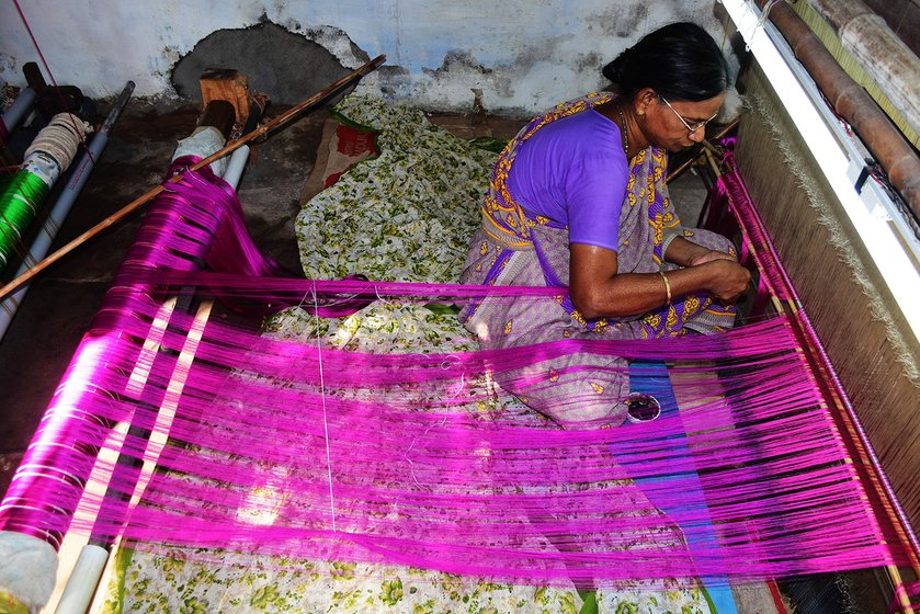 Saraswathi Eswarayan fixes the warp to the loom, traditionally called 'paavu punaithal'. This task is usually done by women, who twist 4,500-4,800 strands by hand on the loom.