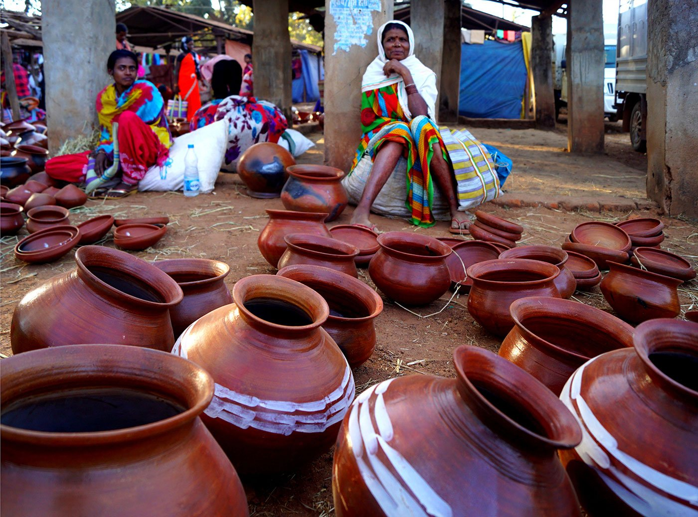 Two women wait with their pots for customers