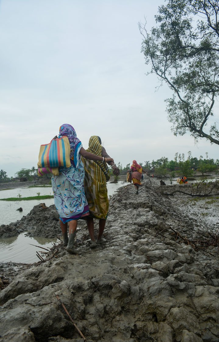 Left: Women of Kalidaspur village, Chhoto Molla Khali island, Gosaba block, returning home after collecting relief items from a local organisation. Right: Children playing during the high tide in Baliara village on Mousuni island. Their fathers work as a migrant labourers in the paddy fields of Uttarakhand.