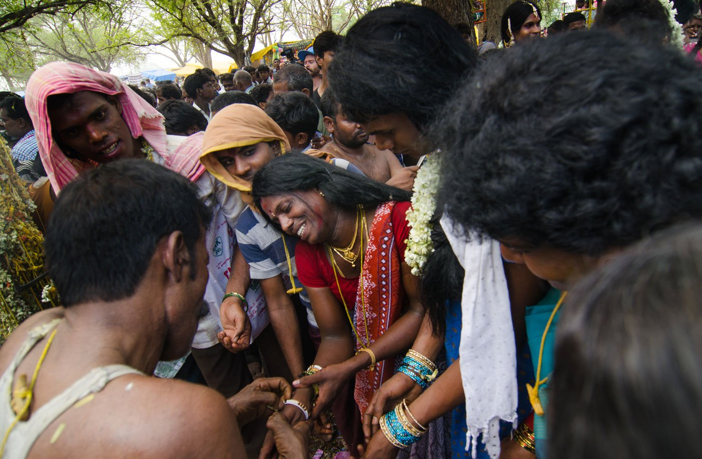 A priest breaks an aravani's bangles – one of the rituals of widowhood. Visibly distraught, she begins to sob.  Many visitors stand around watching the rituals
