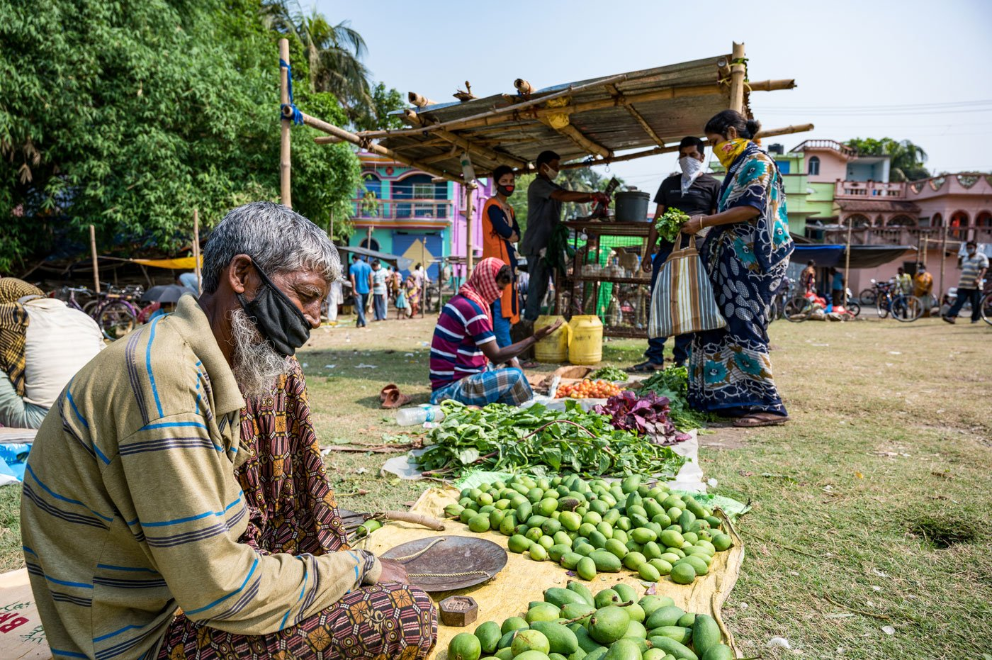 Sadhu Shaikh, 56, has found a spot just off the filed, away from where the other vendors are sitting. He is selling mangoes and vegetables from his own small farmland.