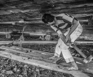 A labor is repairing bottom of a dhow