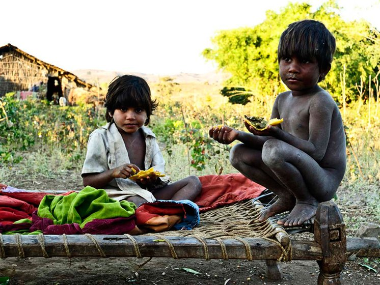 In Attha village, Amashia Budla, 6, and his little sister, Retli, eat rotis made the previous day. Most of the villagers eat leftover rotis the next morning with crushed red chilli and edible oil