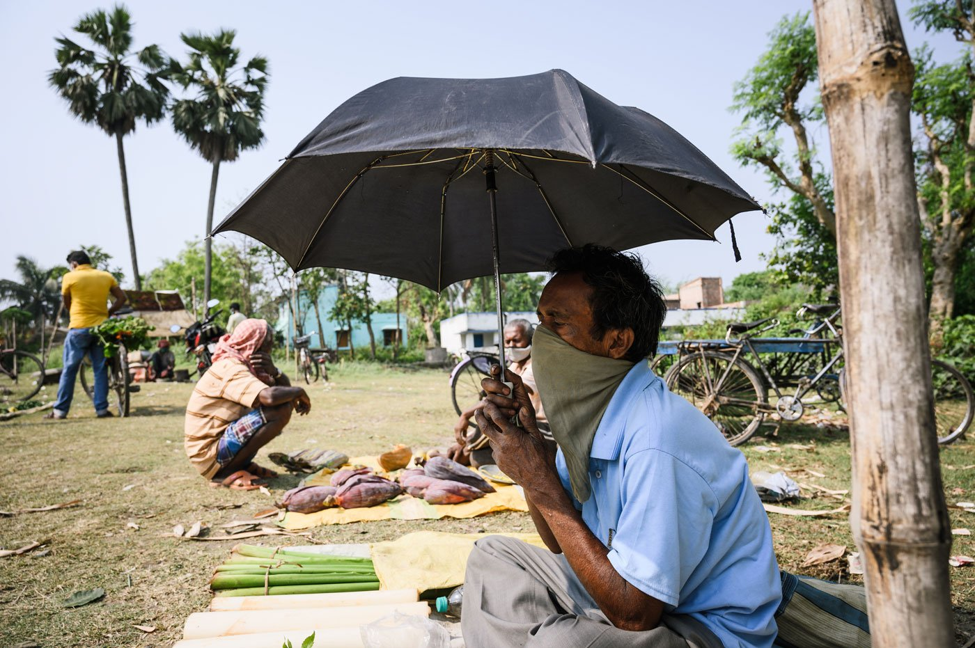 "Without a plastic sheet to use as a temporary shade from the sun, Sadananda Roy, 58, sits in middle of the field with a few vegetables holding an umbrella. He was a domestic worker in Delhi, but came home before the lockdown. His only income now is from selling a few vegetables, which fetches him Rs 50-100 a day. ""I didn't come here regularly because some days I don't have vegetables to sell,"" he says. ""I don't know what will happen in the future."""