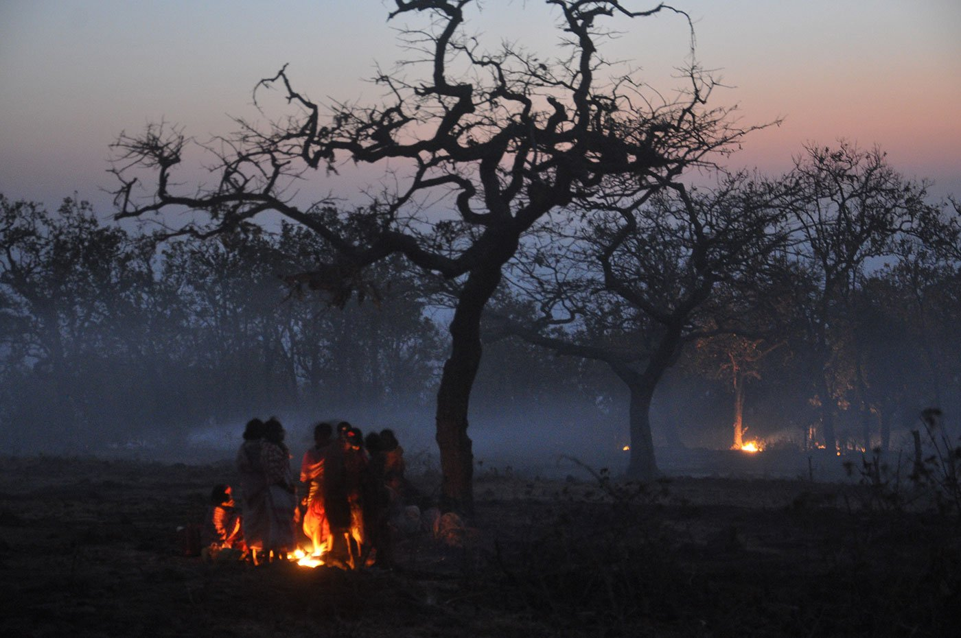 Tribals huddled next to a campfire in the evening