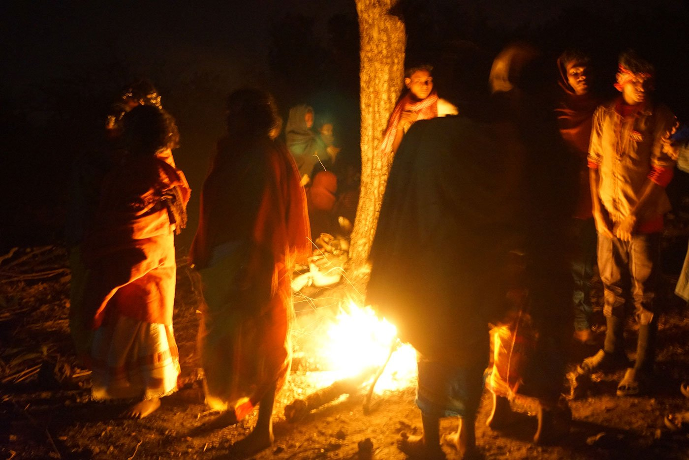 Tribals standing around a campfire at night