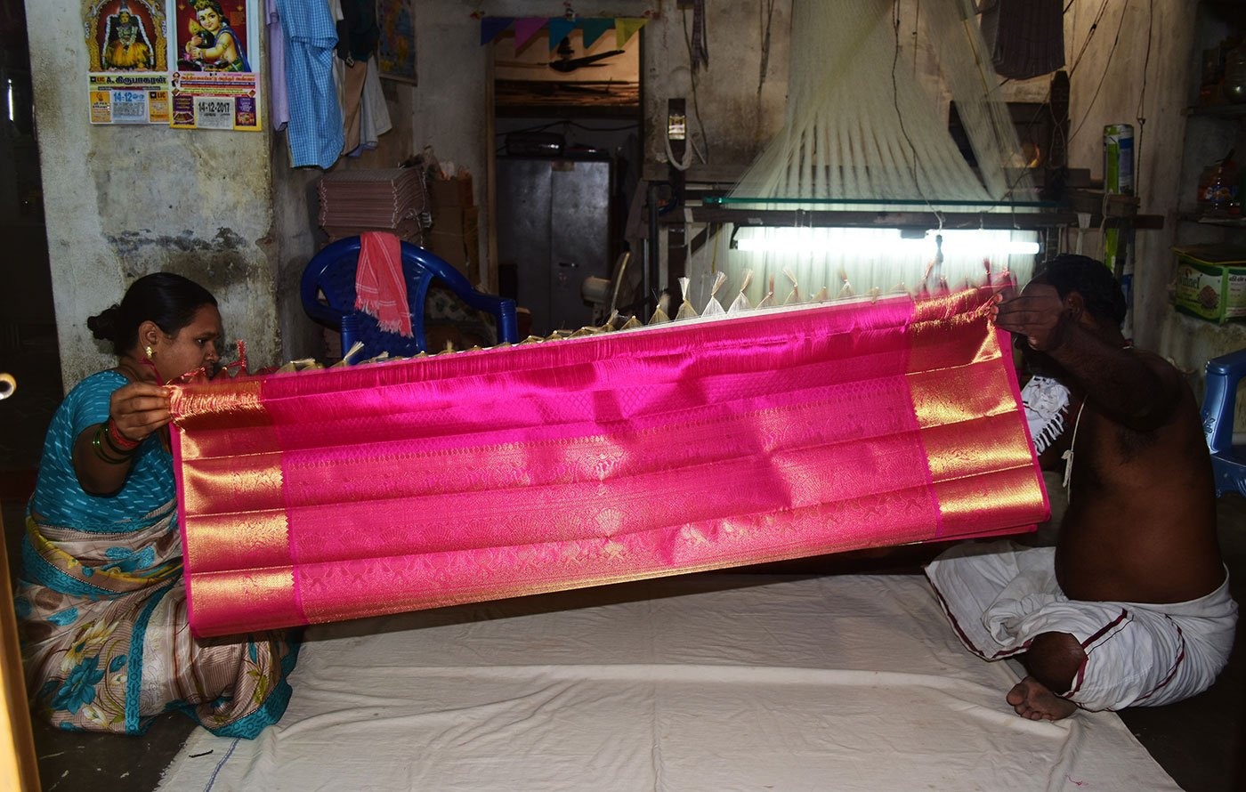 Devasenathipathi Kothandapani (another weaver by same name) and his wife Gomathi pack the finished saree into a box. The weavers have to deliver the neatly folded and boxed sarees to the cooperatives they are associated with