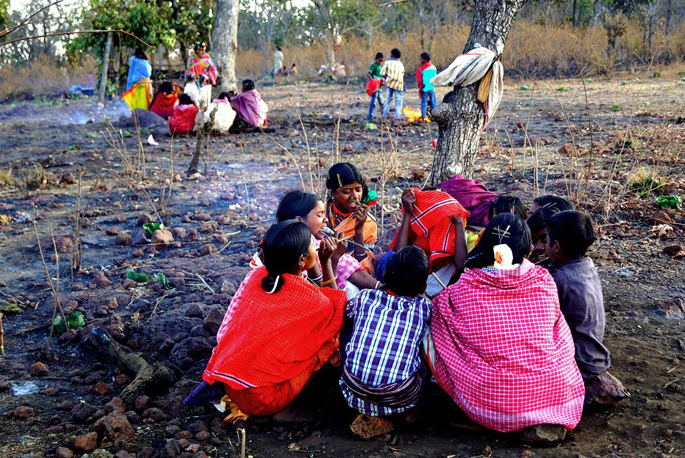 Groups of tribals sitting on the ground after the festivities